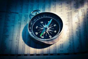Kompass liegt auf einer Zeitschrift mit Zahlen
