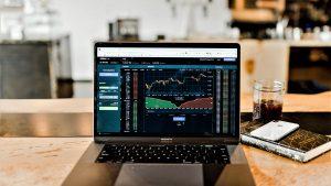 Ein Laptop mit einer Abbildung von Kursverläufen und Trends des Aktienmarktes