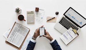 Abbildung einer Person am Tisch sitzend, mit einem Handy in der Hand, Laptop, Taschenrechner und einer Wirtschaftszeitung