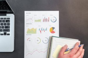 Person mit Hand auf einem Block und Stift, darunter ein Chart mit verschiedenen Diagrammen