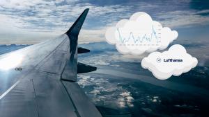 Ausblick auf den Flügel des Lufthansa Flugzeuges während des Flugs. Daneben sind 2 Wolken mit jeweils dem Lufthansa Logo und dem Kursverlauf