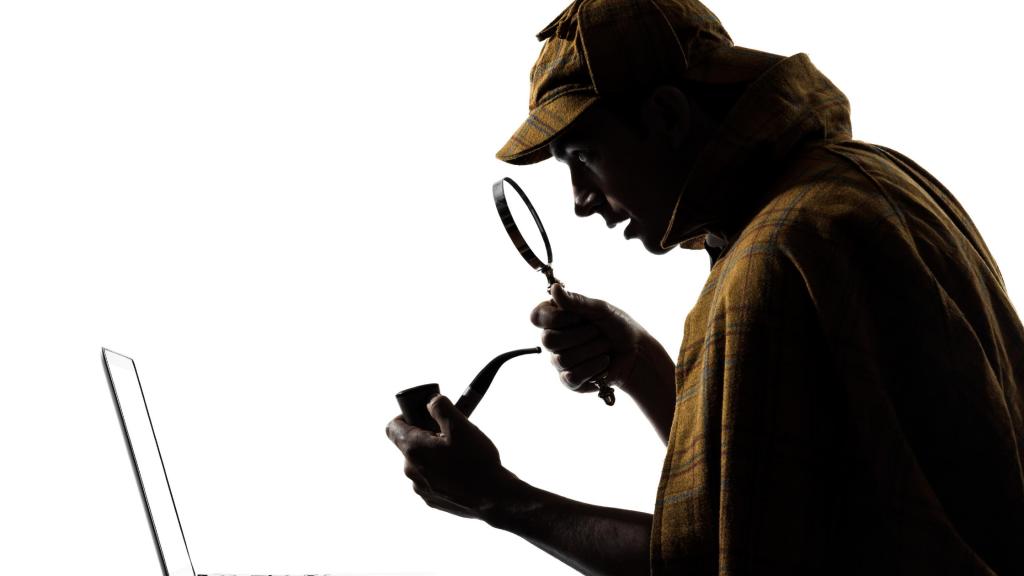 """Person im """"Sherlock"""" - Outfit sitzt vor dem Laptop mit Lupe und Pfeife"""