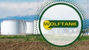Öllager und Berge im Hintergrund, Logo von Wolftank im Vordergrund